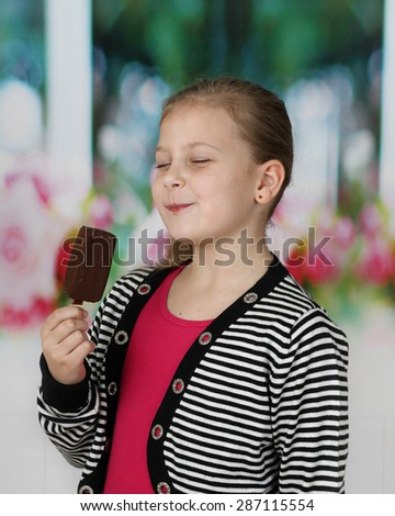 Cute little girl eats ice cream with pleasure expressed on her face - stock photo