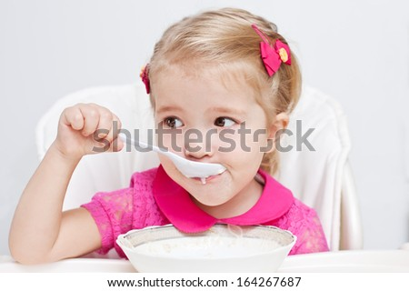 cute little girl eats with a spoon milk porridge while sitting at table on white background