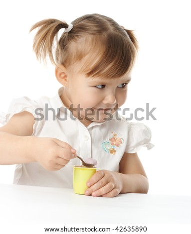 Cute little girl eats yogurt, isolated over white
