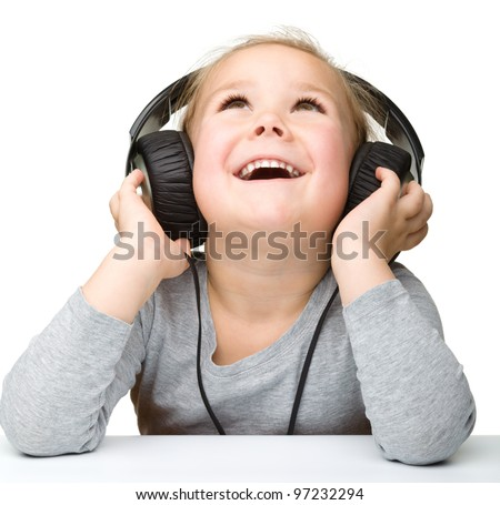 Cute little girl enjoying music using headphones, isolated over white - stock photo