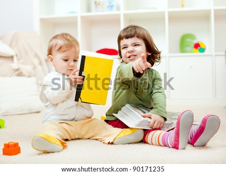 Cute little girl expressing discontent and her baby bother reading - stock photo
