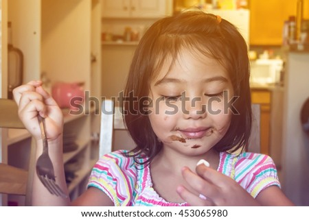 cute little girl feeling happy and getting messy face while eating chocolate and marsh mellow in dining room with blurred background, filtered color tone - stock photo