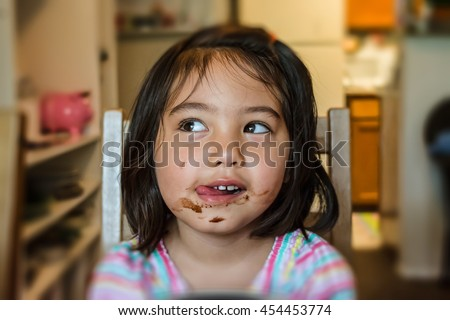 cute little girl feeling happy and getting messy face while eating chocolate in dining room with blurred background - stock photo