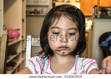 cute little girl feeling sad and getting messy face while eating chocolate in dining room with blurred background - stock photo