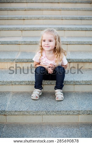 cute little girl for a walk sitting on the steps - stock photo