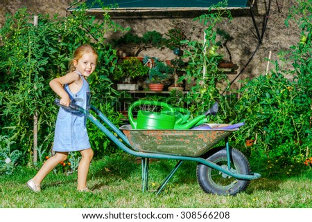 Cute little girl gardening in the backyard. Childhood concept.