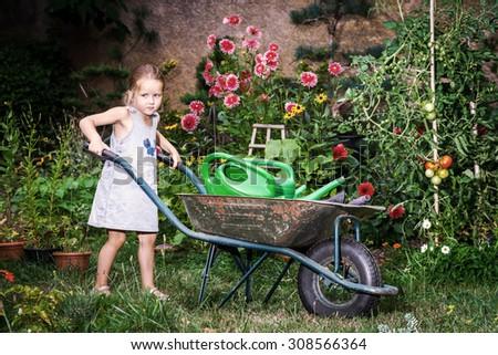 Cute little girl gardening in the backyard. Childhood concept. - stock photo