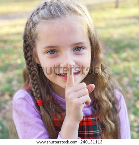 cute little girl gesturing hush sign