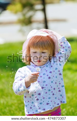 Cute little girl gets dandelion and smiling, happy family having fun  playing outdoor, summer nature