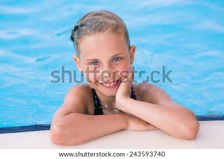 Cute little girl getting out of swimming pool - stock photo