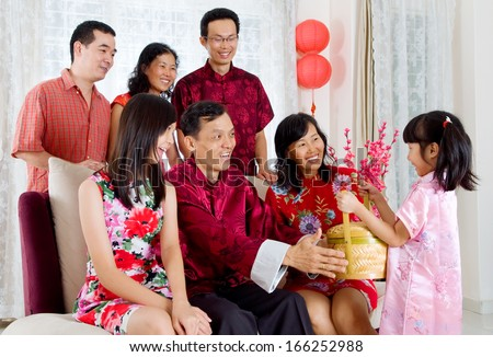 cute little girl giving gift basket to grandparent on chinese new year - stock photo