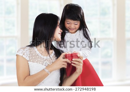 Cute little girl giving present to her mother at home, symbolizing thankful to parent - stock photo