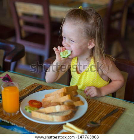 Cute little girl having breakfast at resort restaurant