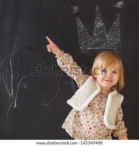 Cute little girl having fun. Chalk drawing on dark background - stock photo
