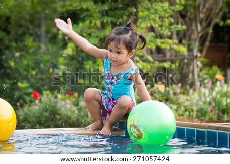 Cute little girl having fun in the swimming pool - stock photo