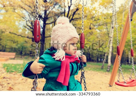 cute little girl having fun on swing at autumn day