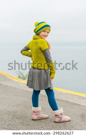 Cute little girl having fun outdoors on a cold day, dancing next to beautiful lake, wearing green woolen pullover, hat and warm boots