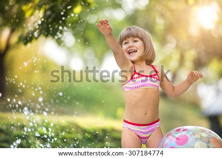 Cute little girl having fun outside in summer garden     - stock photo
