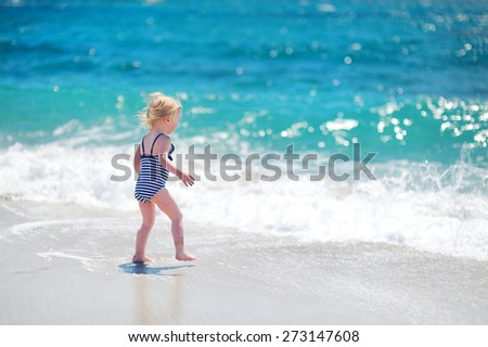 Cute little girl having fun, playing and jumping over the waves on a beautiful sunny beach on Sardinia - stock photo