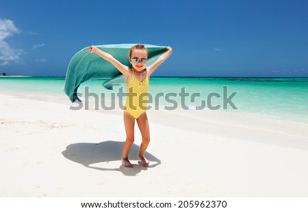 Cute little girl having fun running with towel and enjoying vacation at tropical beach on white sand and turquoise ocean water  - stock photo