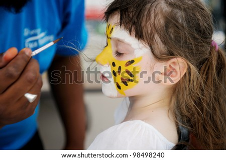 Cute little girl having her face painted on a hot summer day - stock photo