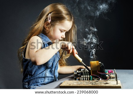 Cute little girl helping father to repair old computer motherboard using solderer