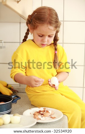 Cute little girl helps in the kitchen preparing lunch - stock photo