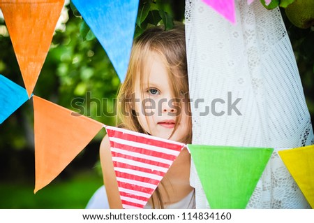 Cute little girl hiding among party garlands in the garden - stock photo