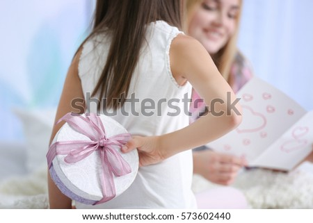 Cute little girl hiding present for her mother behind back, close up. Mother's day concept