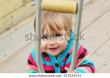 Cute little girl holding a big crutch and looking up, outdoor portrait - stock photo
