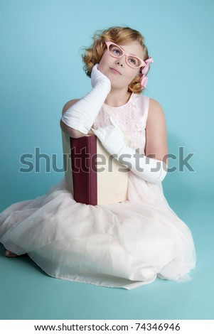 Cute little girl holding a book daydreaming