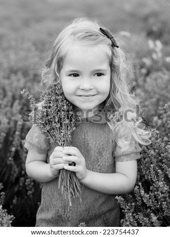 cute little girl holding a bouquet of lavender ( black and white )