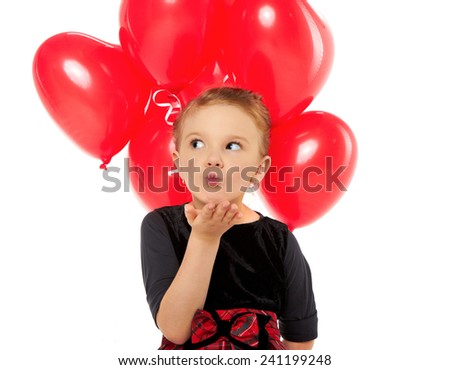Cute little girl holding a bunch of red heart-shaped balloons