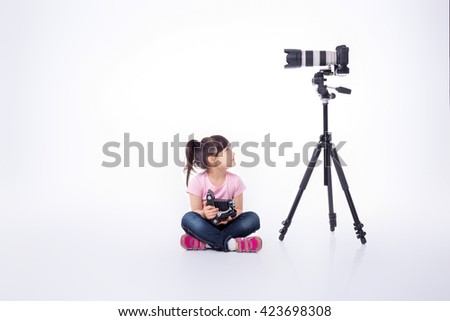 cute little girl holding an old camera, and next is a digital  professional camera on a tripod. old and modern technology - stock photo