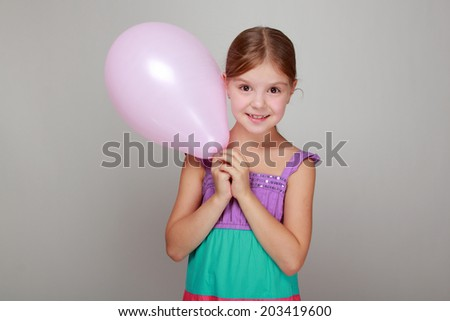 Cute little girl holding balloon on a gray background on Holiday