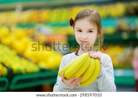 Cute little girl holding bananas in a food store or supermarket - stock photo