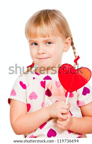 Cute little girl holding big red heart shaped lolly pop candy