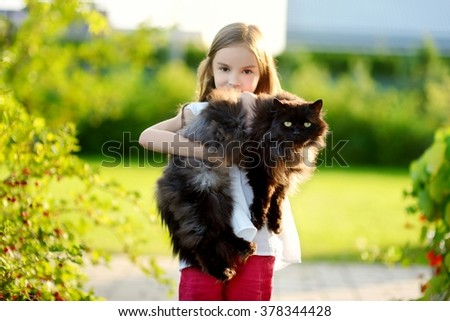 Cute little girl holding giant black cat outdoors - stock photo