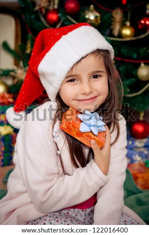 Cute little girl holding gift box in front of christmas tree - stock photo