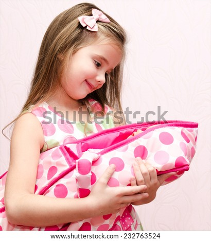 Cute little girl holding her doll isolated - stock photo