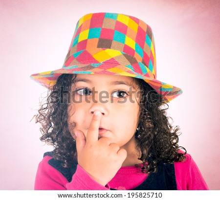 Cute little girl holding her finger on lips - stock photo