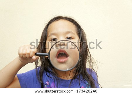 Cute little girl holding magnifying glass - stock photo