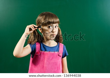 Cute little girl holding magnifying glass in front of blackboard,Schoolgirl with magnifying glass - stock photo