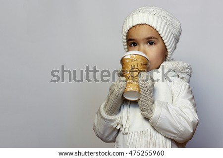 Cute little girl holding mug and drinking tea in white coat, white knitted hats, scarves and mittens over white background, winter outfit