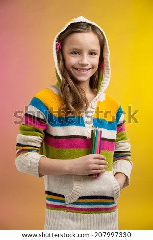 cute little girl holding pencils. pretty schoolgirl standing on yellow background and smiling - stock photo