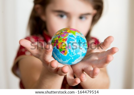Cute little girl holding World Globe on her Hands - stock photo