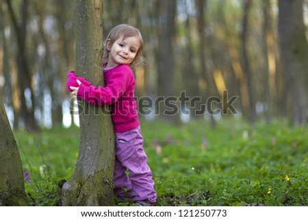 Cute little girl hugging a tree trunk in the spring forest