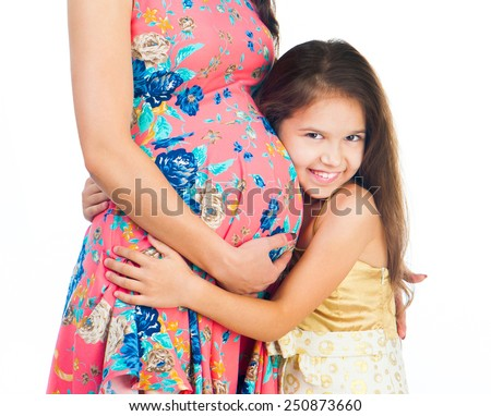 cute little girl hugging belly pregnant mom - stock photo