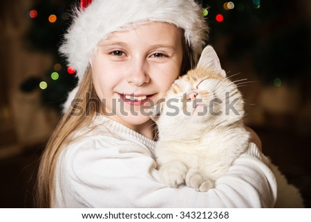 Cute little girl hugging her cat in Christmas - stock photo