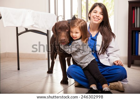 Cute little girl hugging her healthy dog after a visit to the veterinarian - stock photo